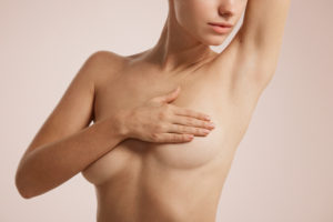 woman holding breasts while posing nude